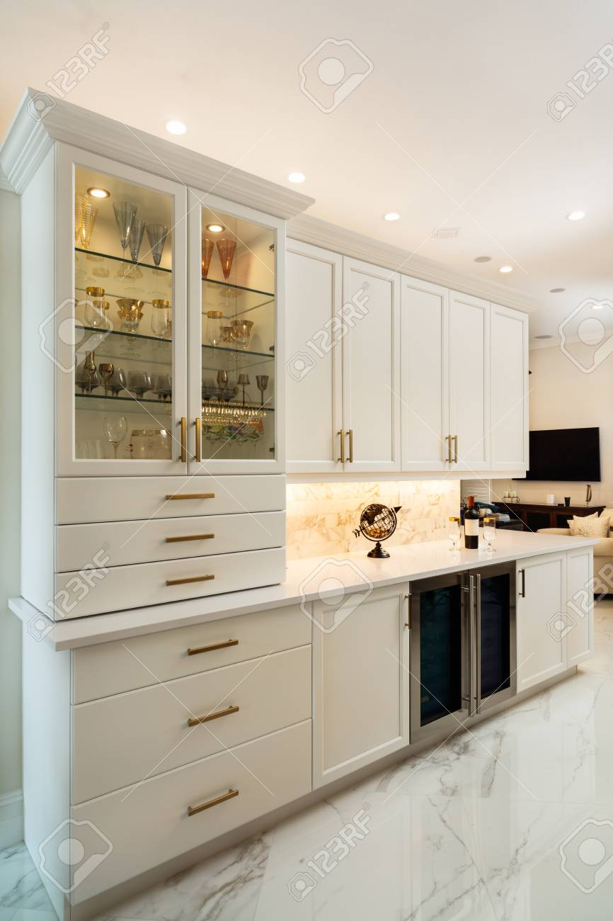 Beautiful luxury home kitchen bar with white cabinets and wine..