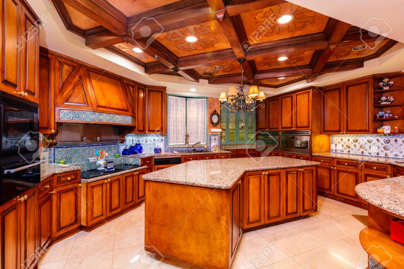 Beautiful luxury home kitchen with red cherry wood cabinets.