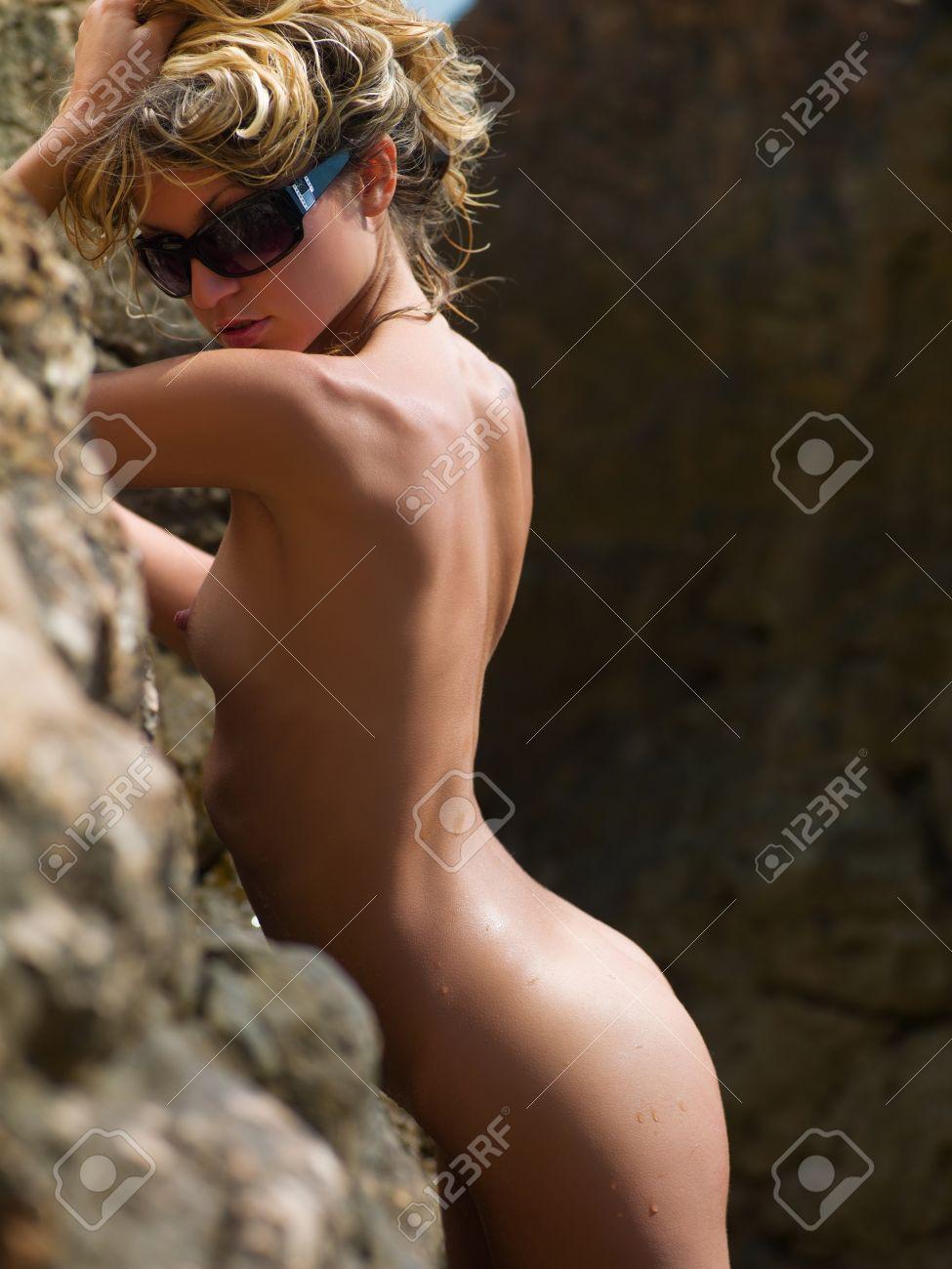beautiful nude woman standing near a rock on the beach Stock Photo - 9143847