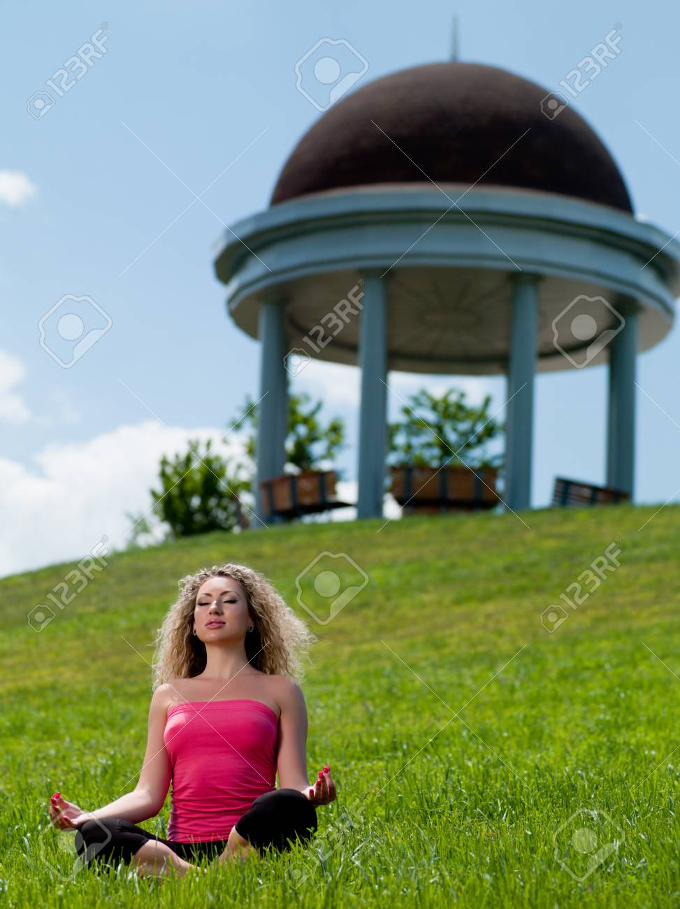 young woman sitting on the grass against the sky Stock Photo - 9908442
