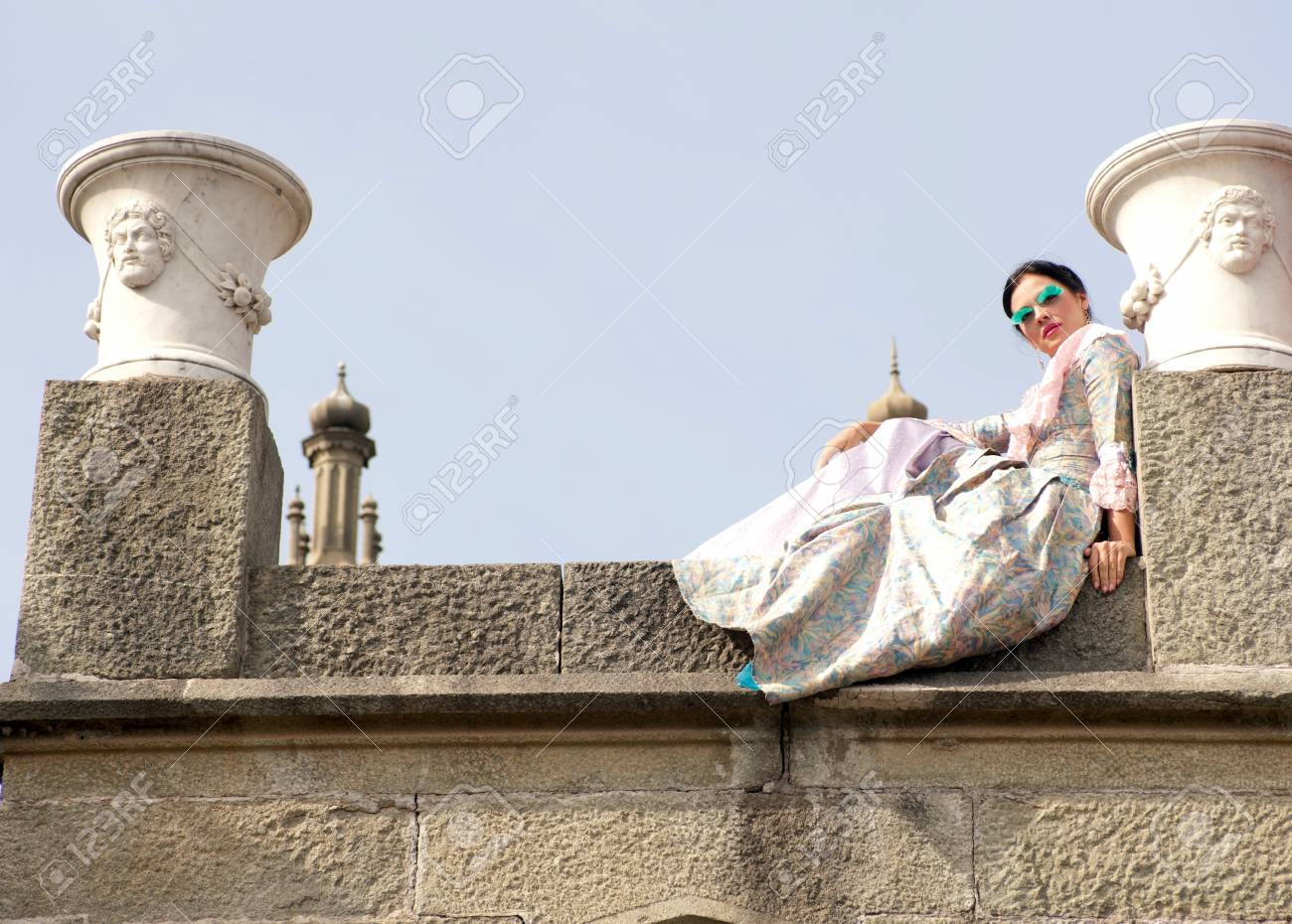 woman in a magnificent dress sitting on a stone slab Stock Photo - 10088463