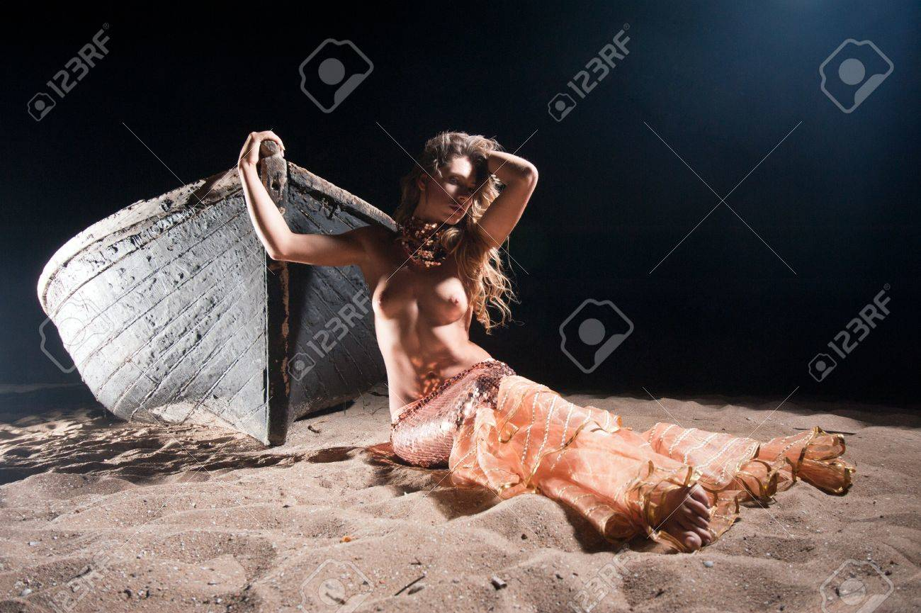 Mermaid girl standing on an old boat on the shore Stock Photo - 17701748