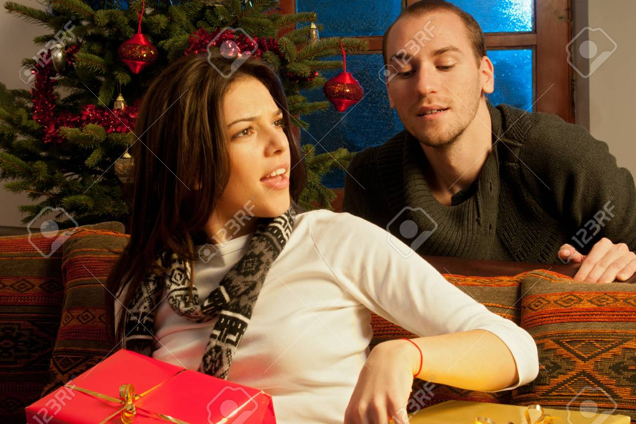 angry girl and curious man having fun with christmas gifts stock photo 11624266