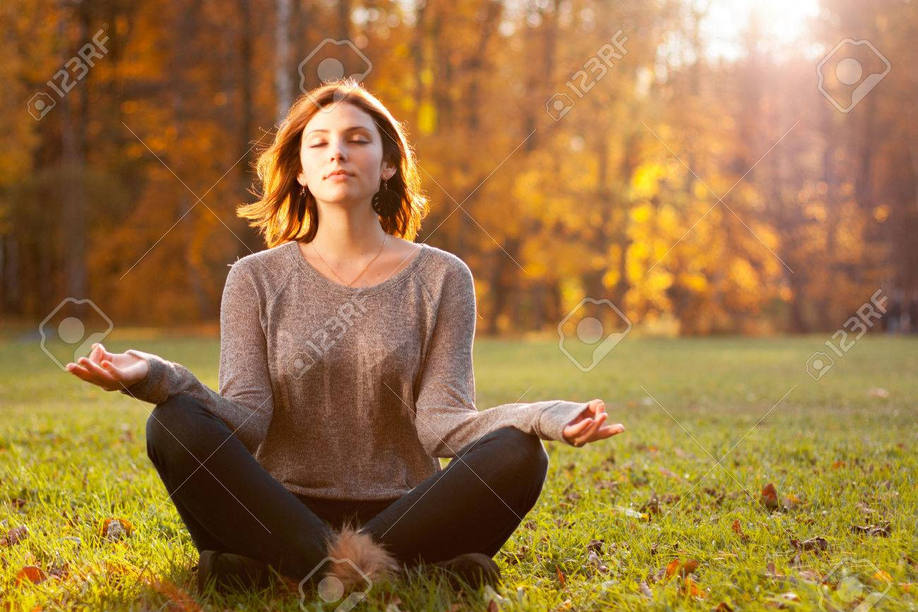Beautiful young girl meditating in autumn park Stock Photo - 24307147