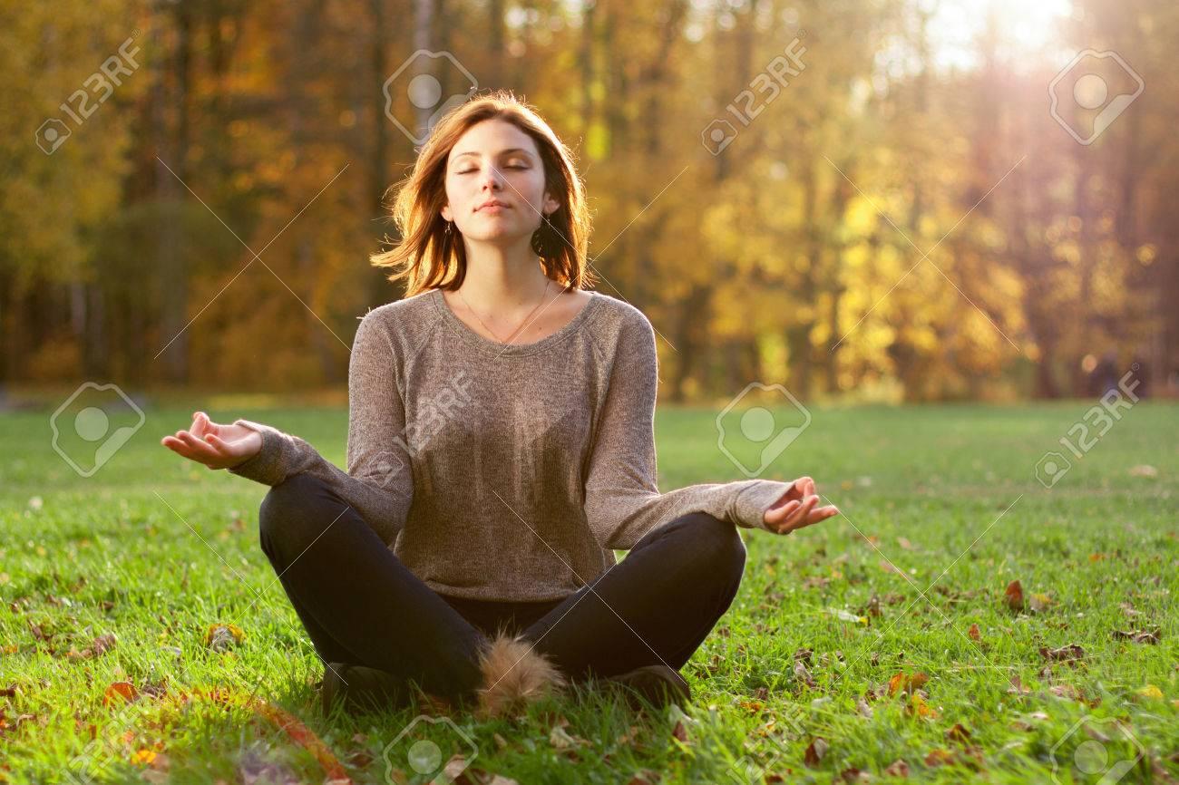 Beautiful young girl meditating in autumn park Stock Photo - 24310492
