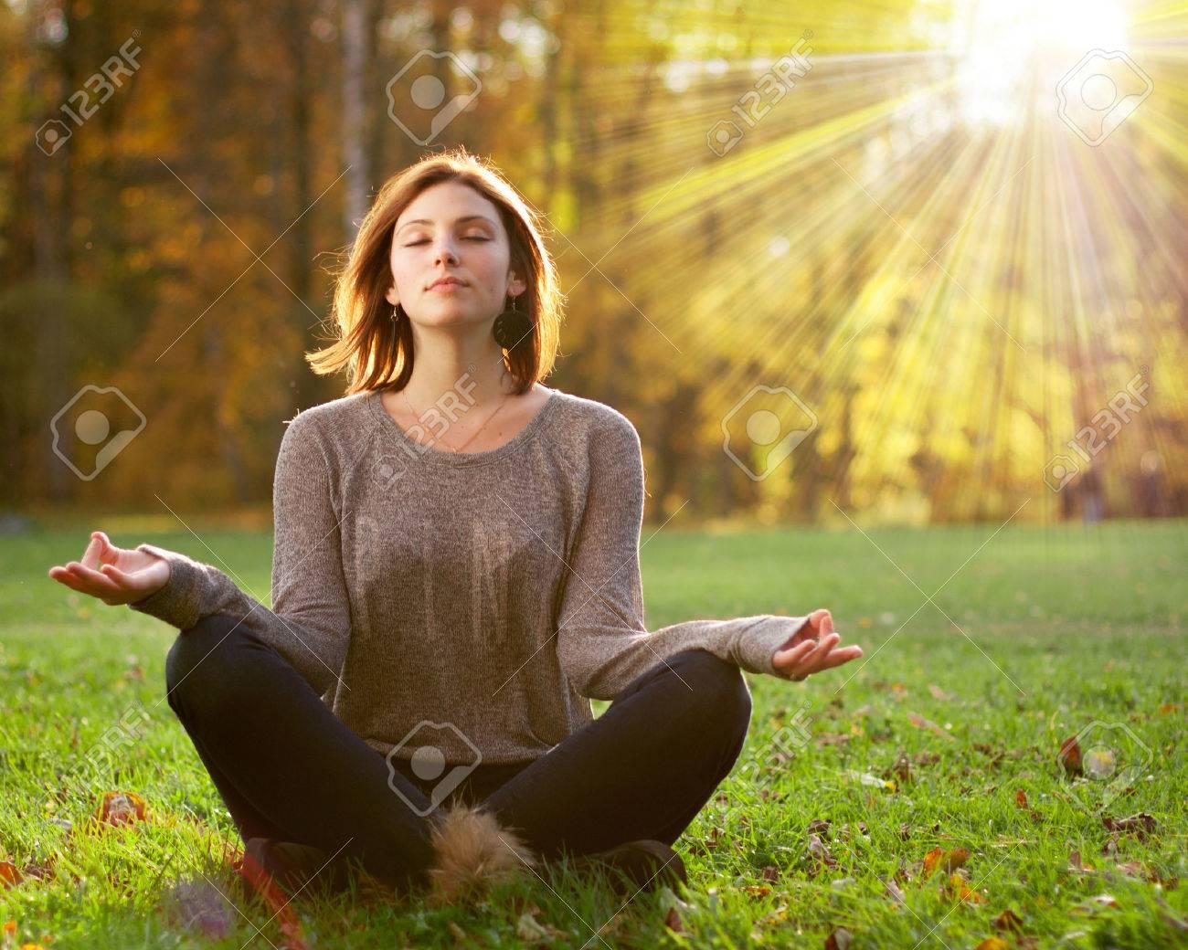 Beautiful young girl meditating in autumn park Stock Photo - 24564720