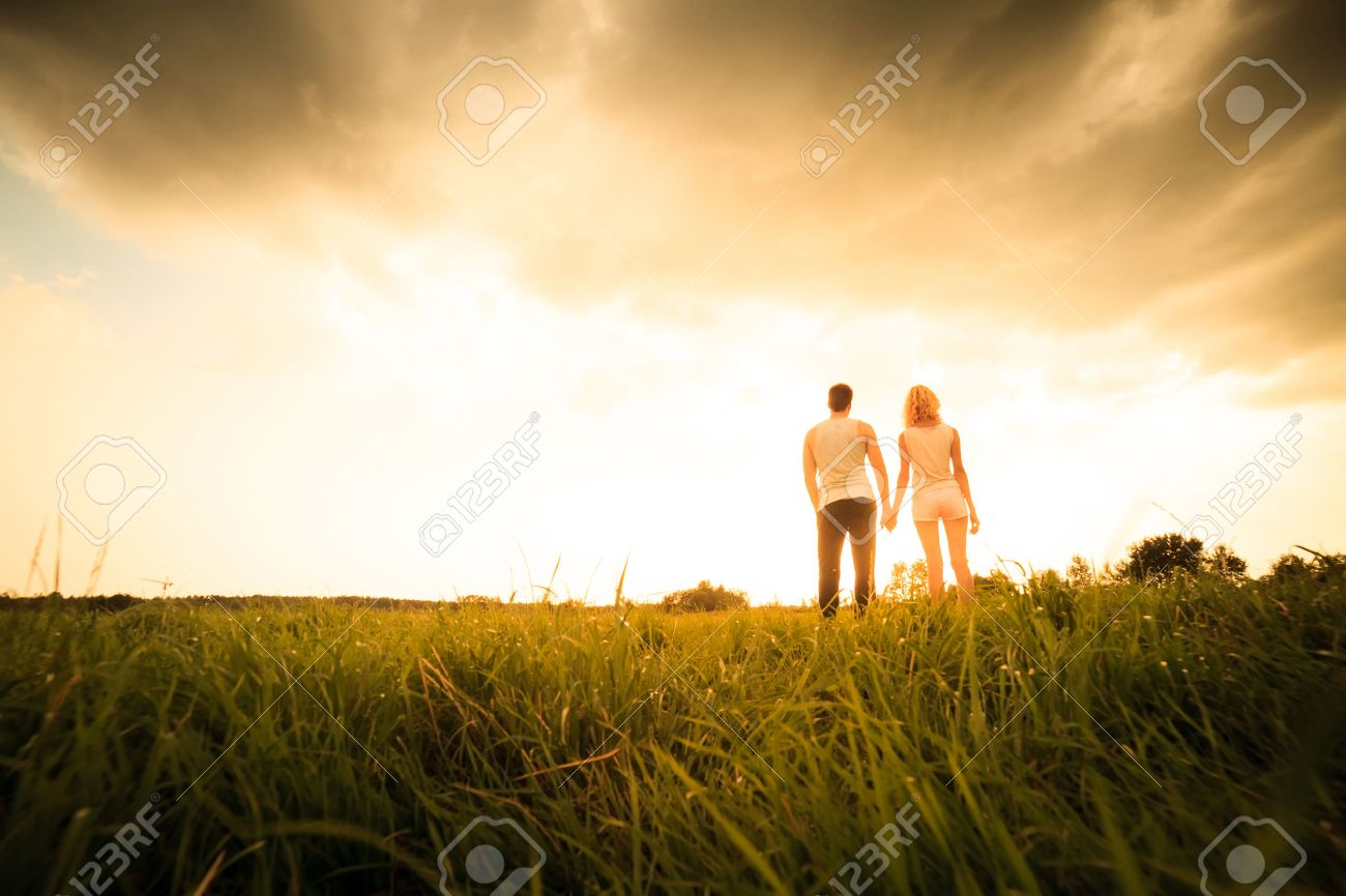 couple walking through the field and holding hands over sunset Stock Photo - 30224325