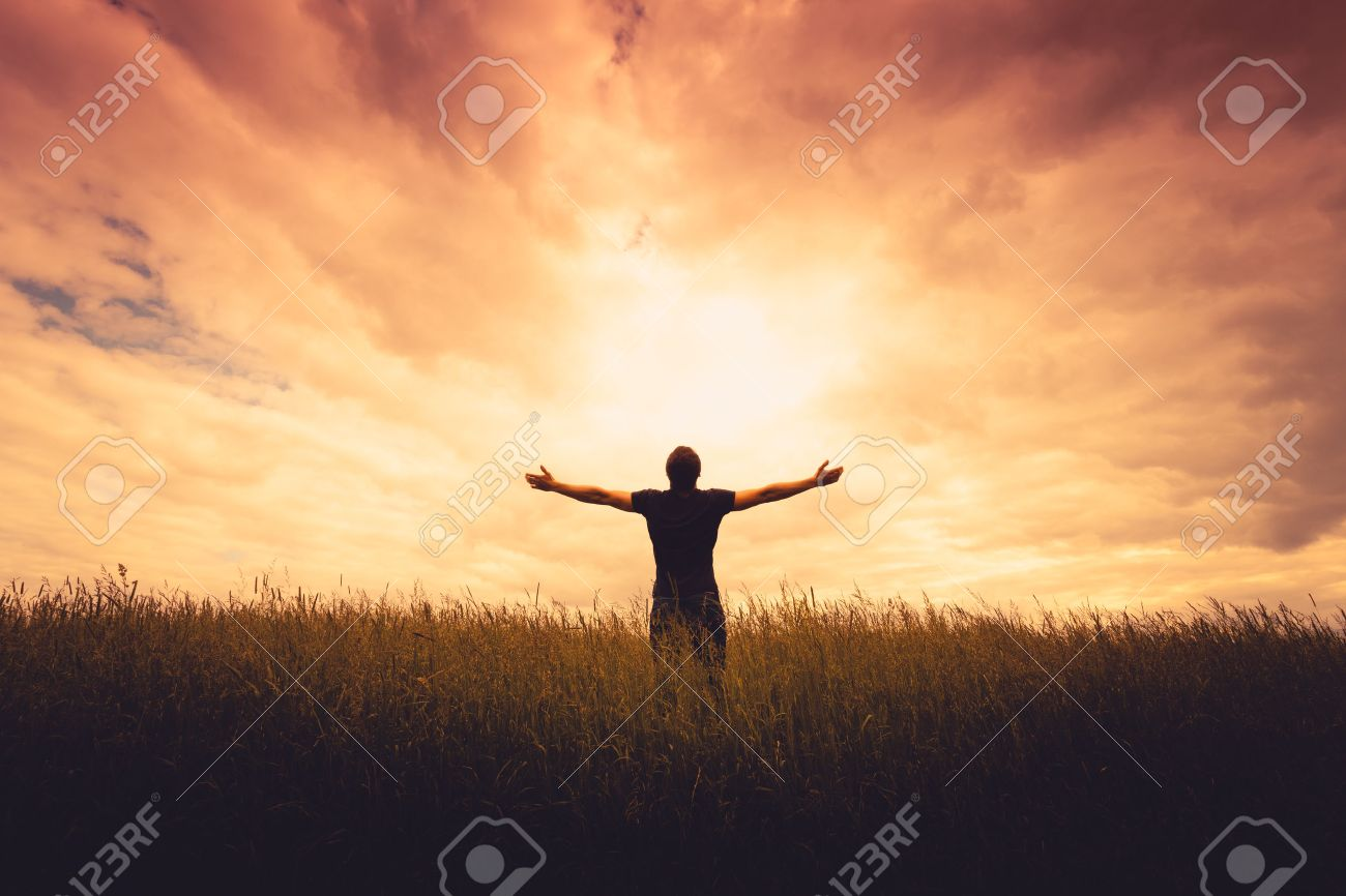 silhouette of man standing in a field at sunset Stock Photo - 42069087