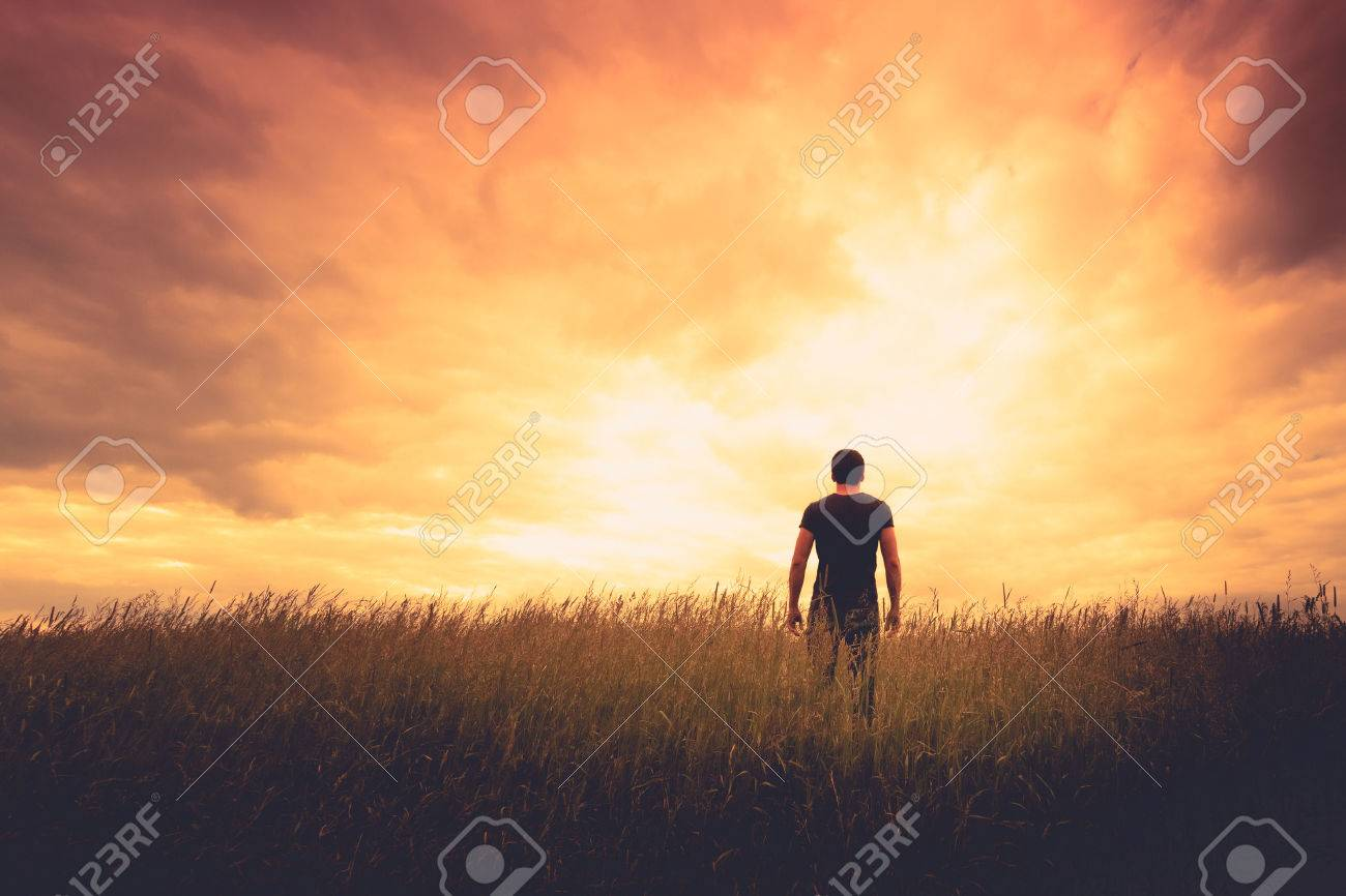 silhouette of man standing in a field at sunset Stock Photo - 42077679