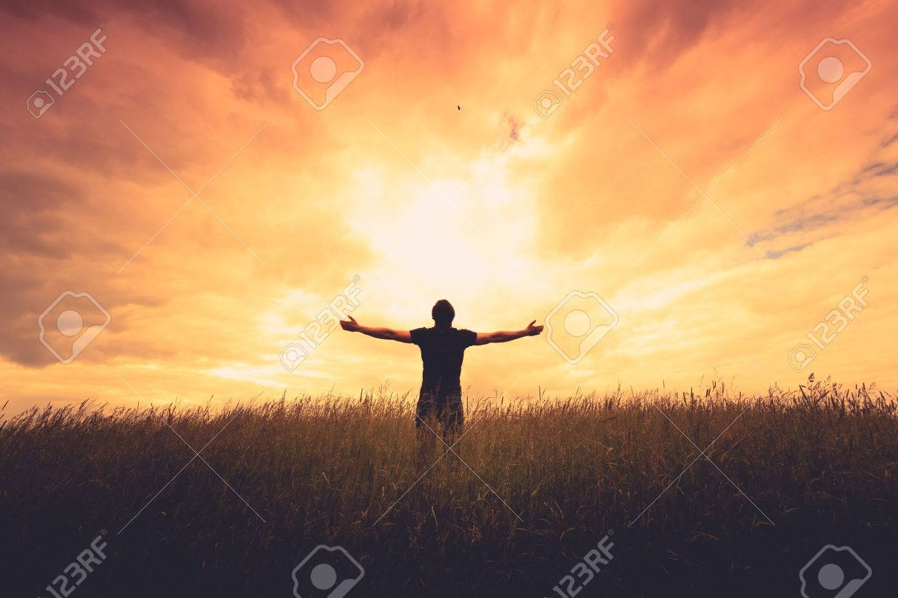 silhouette of man standing in a field at sunset Stock Photo - 42868607