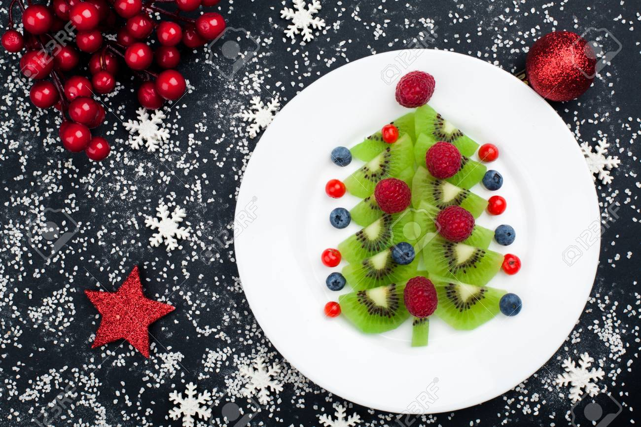 Edible Christmas Tree.Edible Christmas Tree From Kiwi Slices On A Black Plate Over