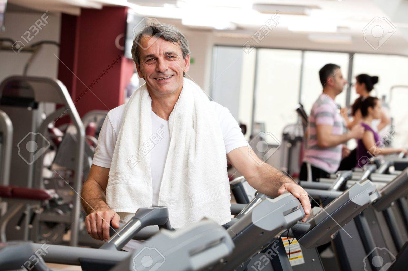 man training in the gym, smiling, with towel around his neck Stock Photo - 14731954