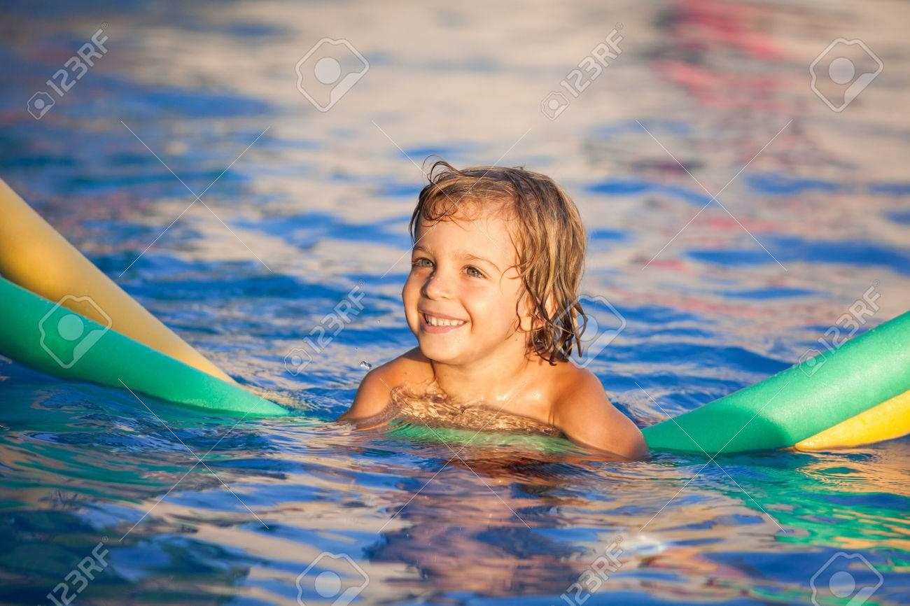 gluckliches kind in den pool das lernen mit schwimmnudel zu schwimmen warmen abendlicht standard