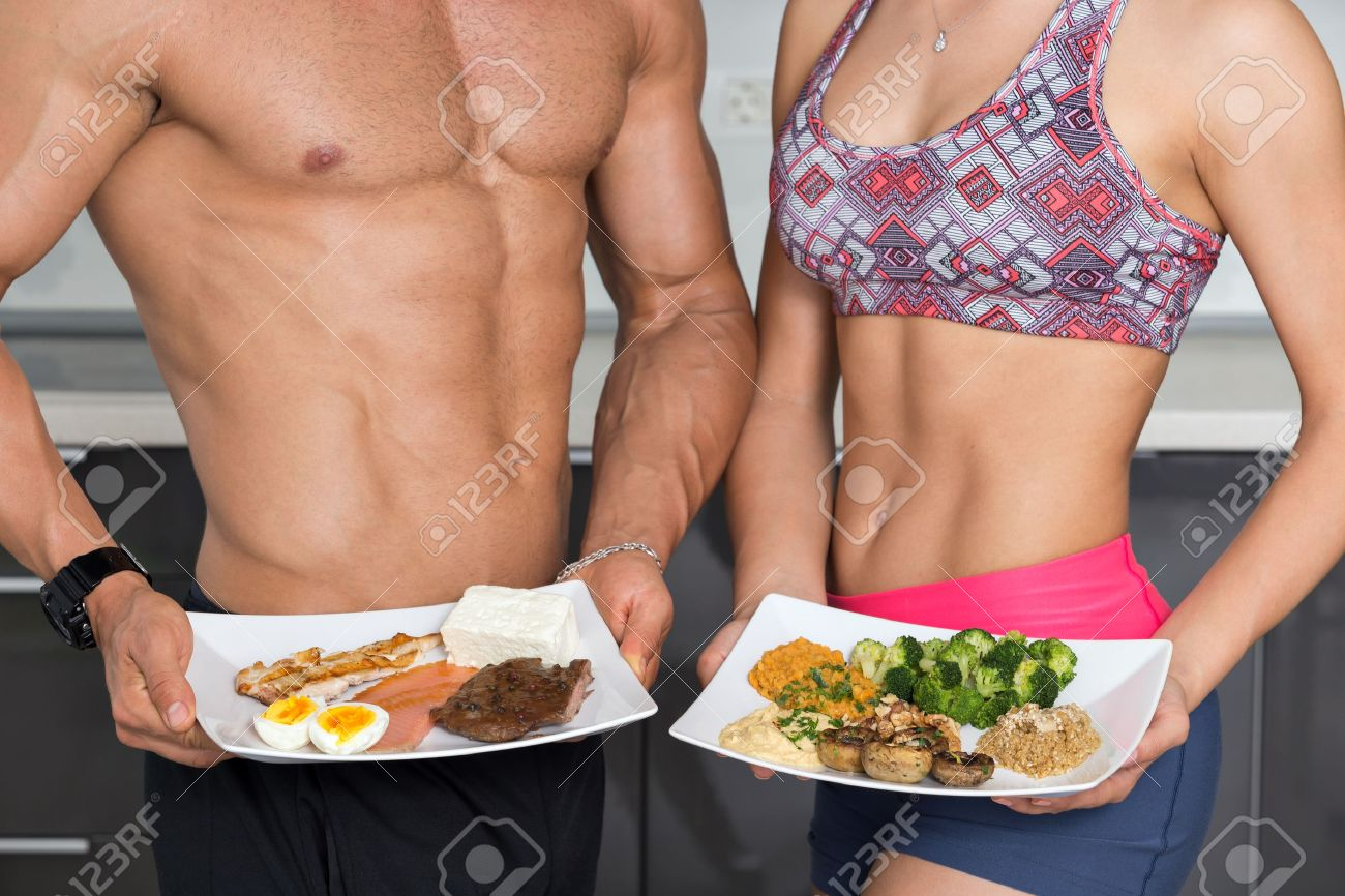 fit couple in the kitchen; animal versus plant proteins: one plate with beef, eggs, salmon, cheese and chicken grill and another with nuts, mushrooms, broccoli, lentil, hummus and quinoa - 57610418