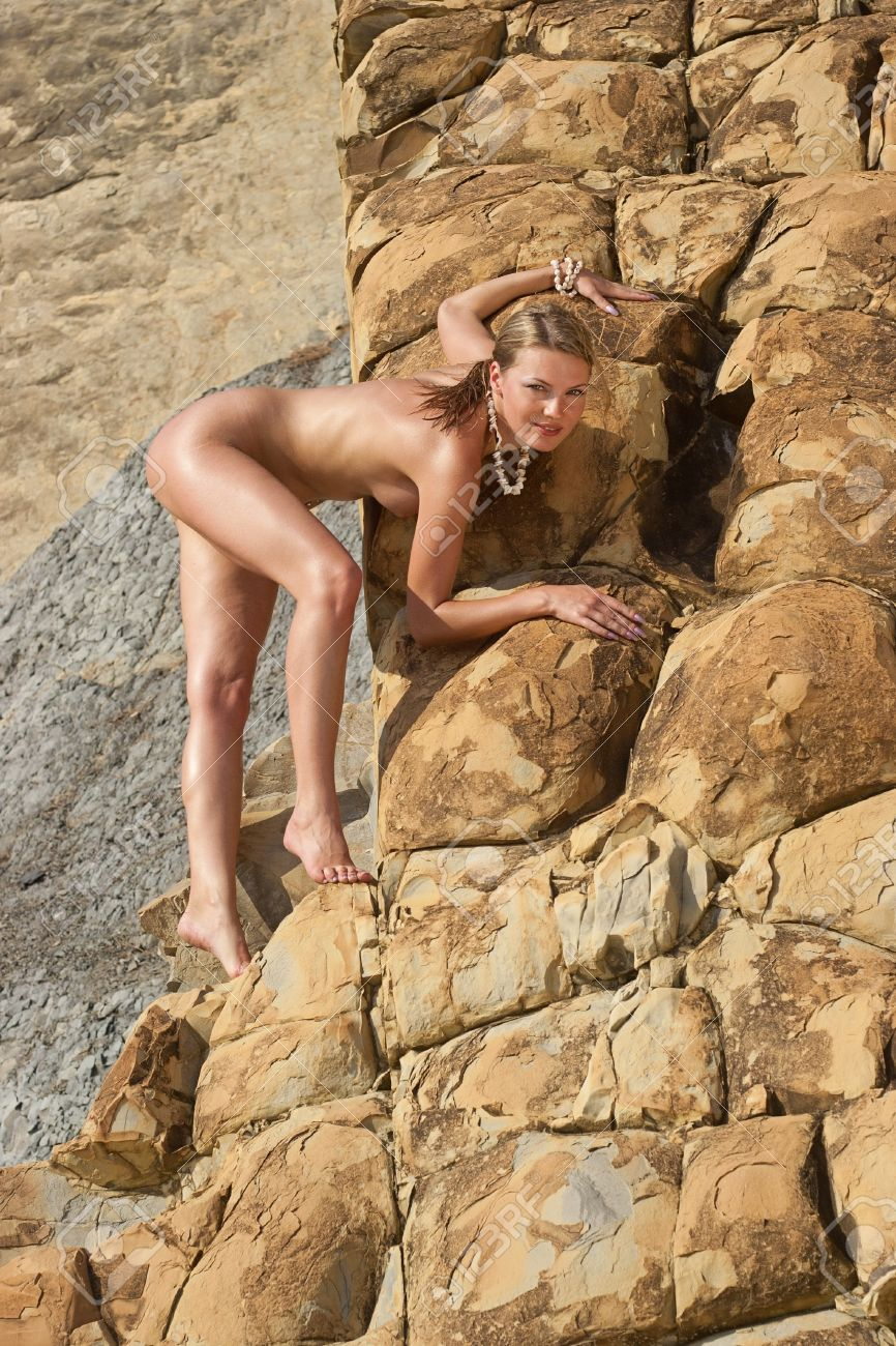 Beautiful nude young woman on the rocks. Stock Photo - 17354728