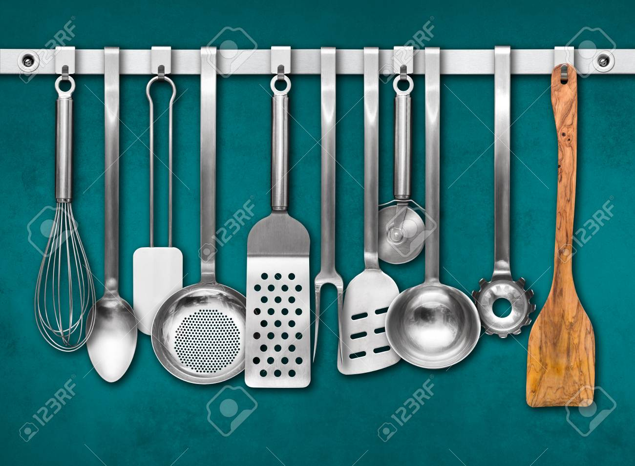 Metal Rail With Kitchen Utensils Hanging In Front Of A Colorful ...