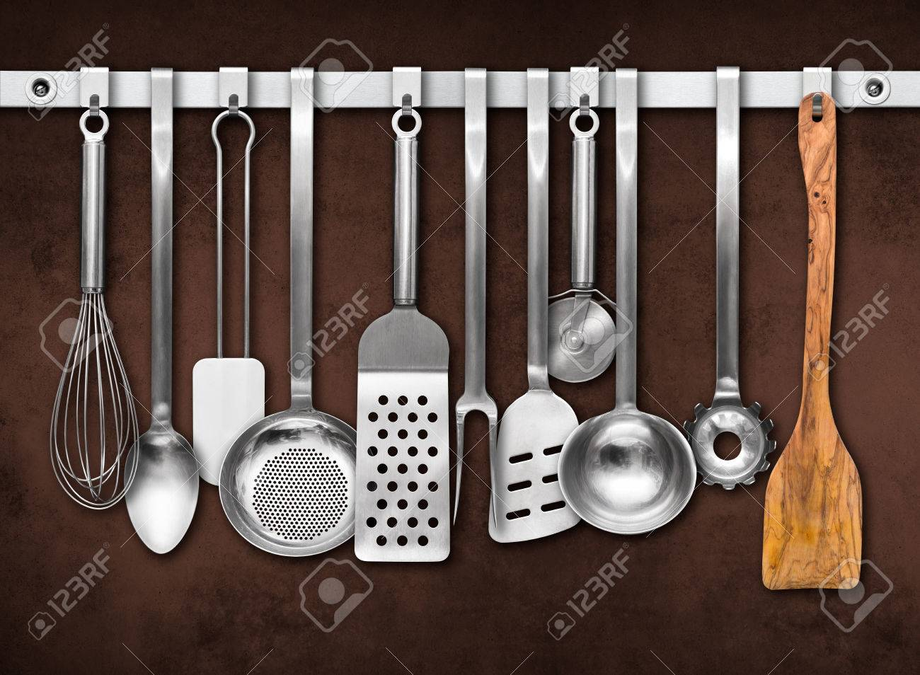 Metal Rail With Kitchen Utensils Hanging In Front Of A Colorful Wall Stock  Photo   44274058