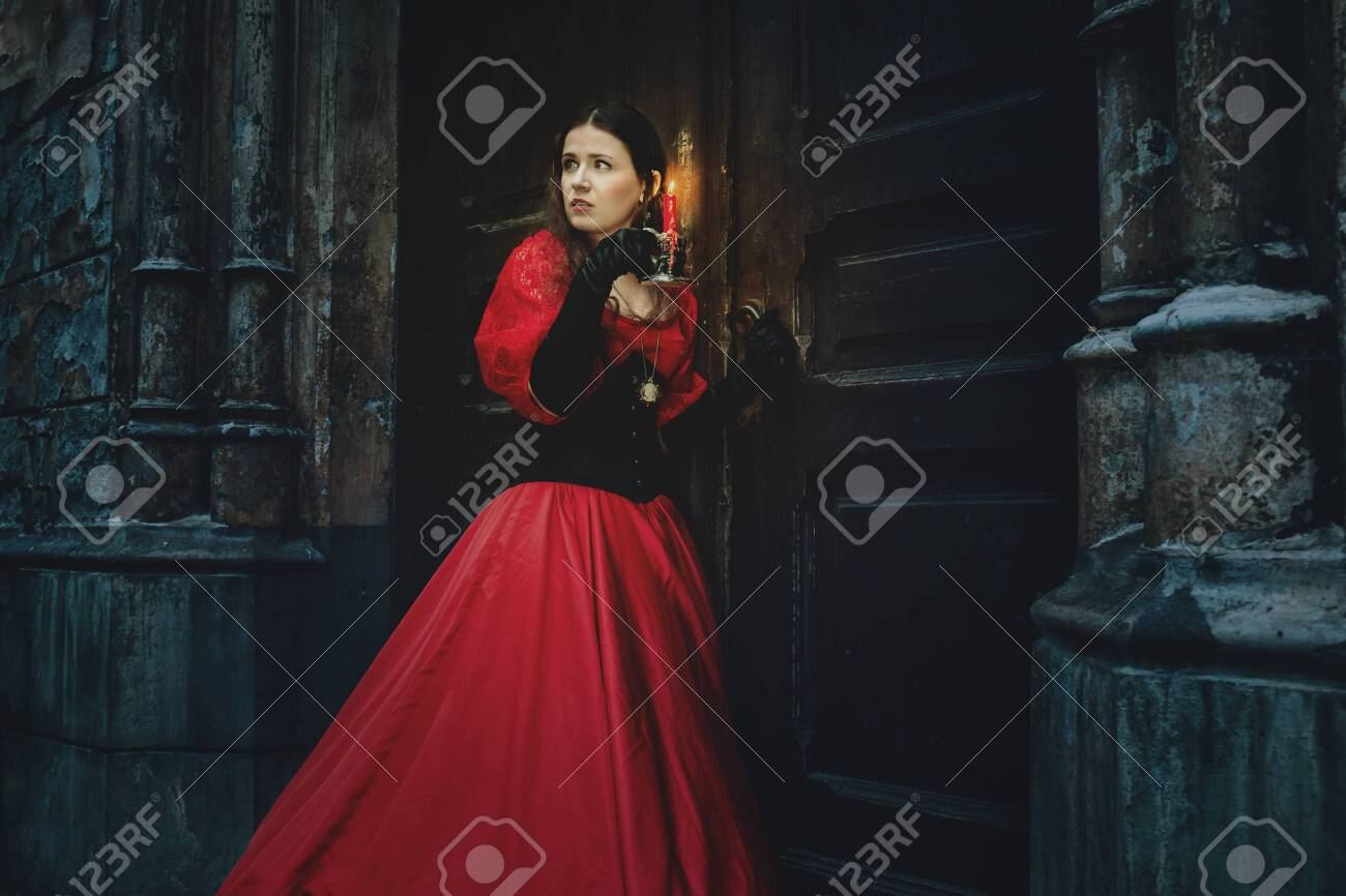 Mysterious woman in a red Victorian dress by the old door - 135385051