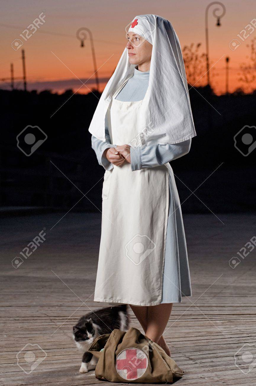Retro styled nurse with cat and first aid kit at sunset Stock Photo - 5942673