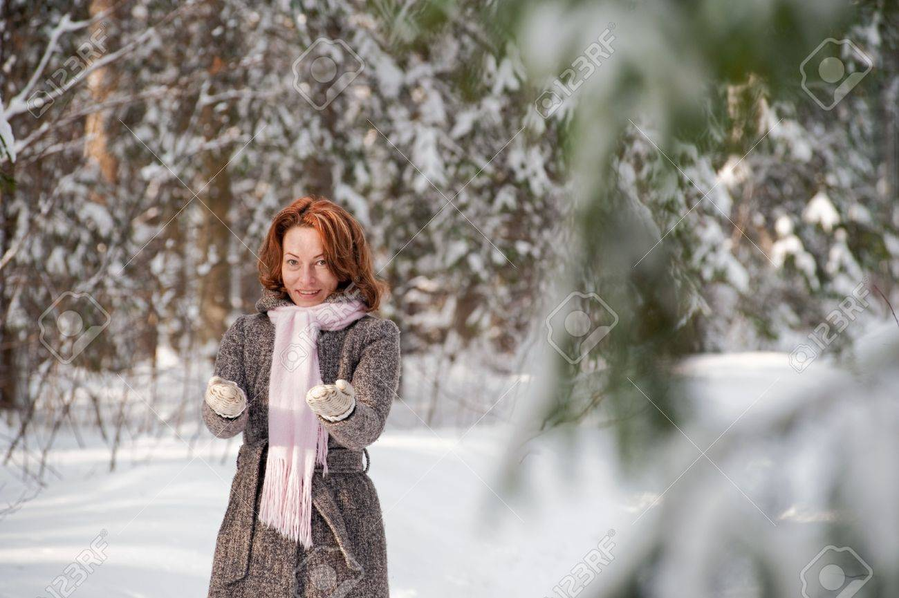 happy red haired woman having fun on winters day in forest stock