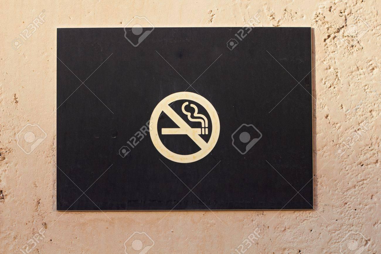 Closeup of no smoking sign warning board on wall - 8720783