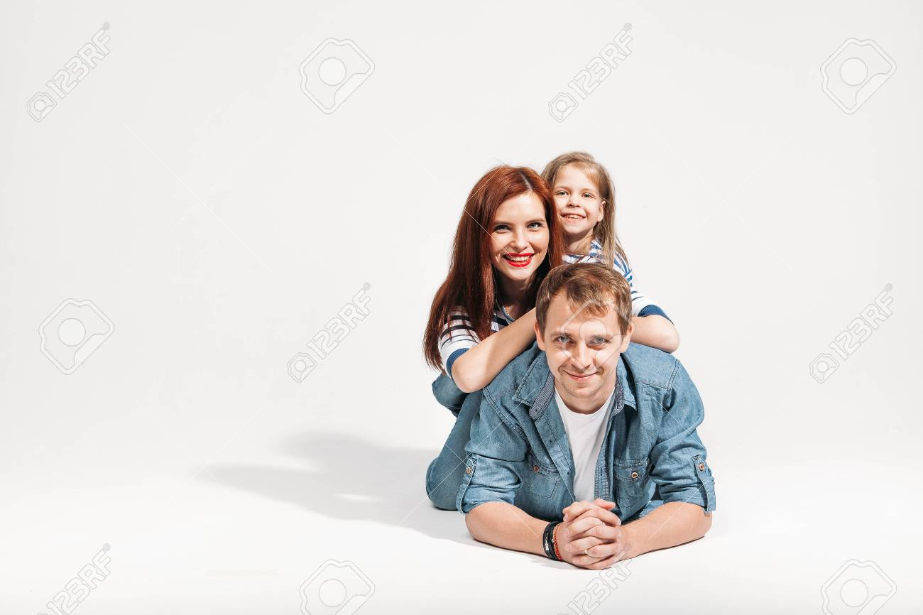 Happy funny family portrait lying on white background isolated on fathers back stock photo 78584017