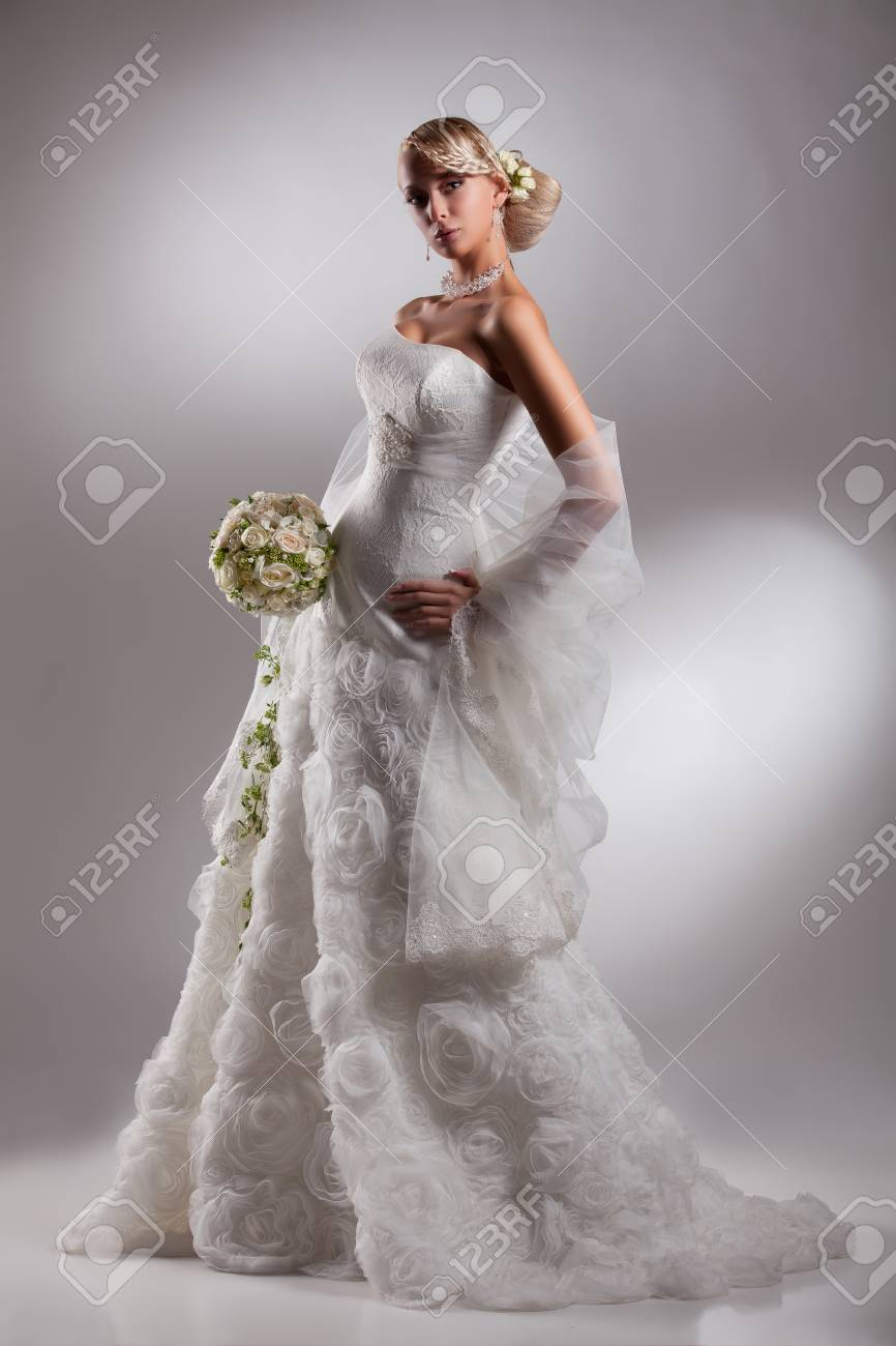 Young Beautiful Blonde Woman In A Wedding Dress On A Studio Background