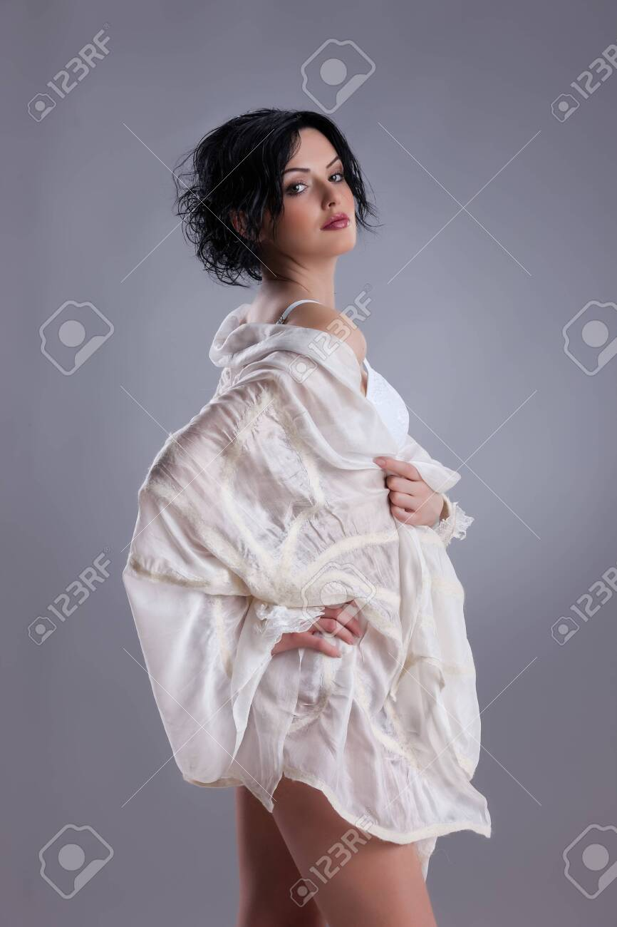 Young beautiful brunette woman in handmade fashionable clothing - 128432240
