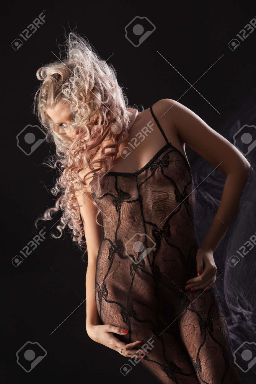 Young beautiful woman in a lingerie on a black studio background - 166442237
