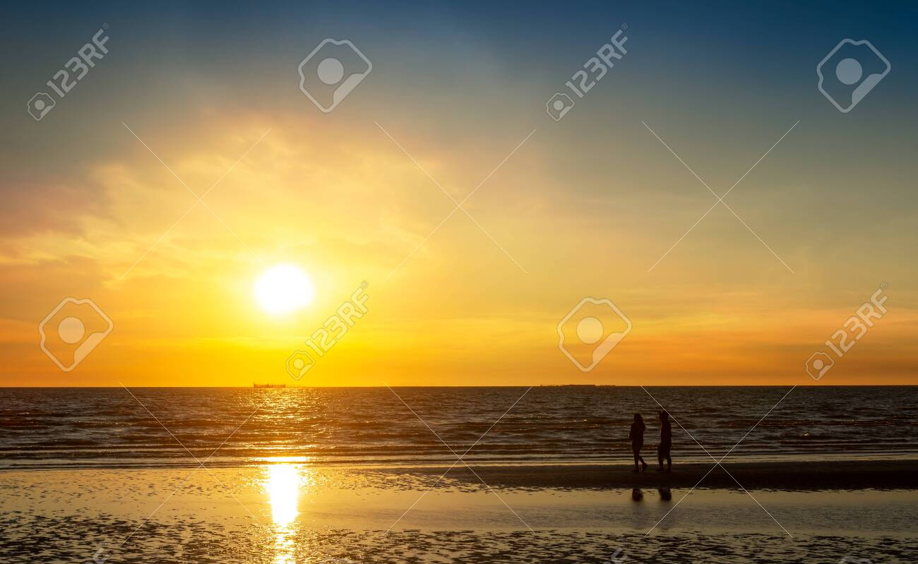 Couple walking at the beach in sunset time, romantic lovers concept - 143567665
