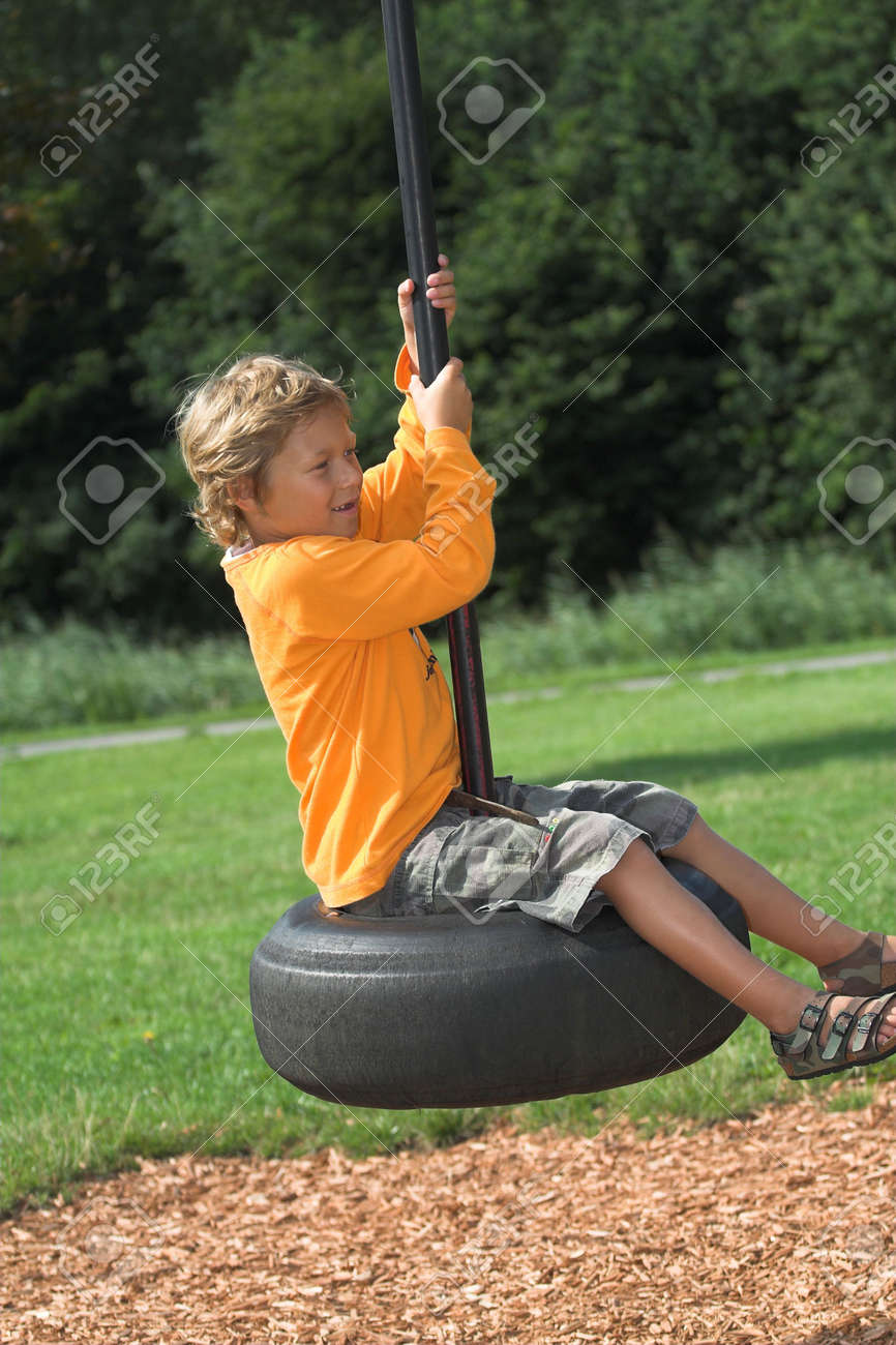 Cute blond boy swinging on a big rubber tyre at the playground Stock Photo - 496592