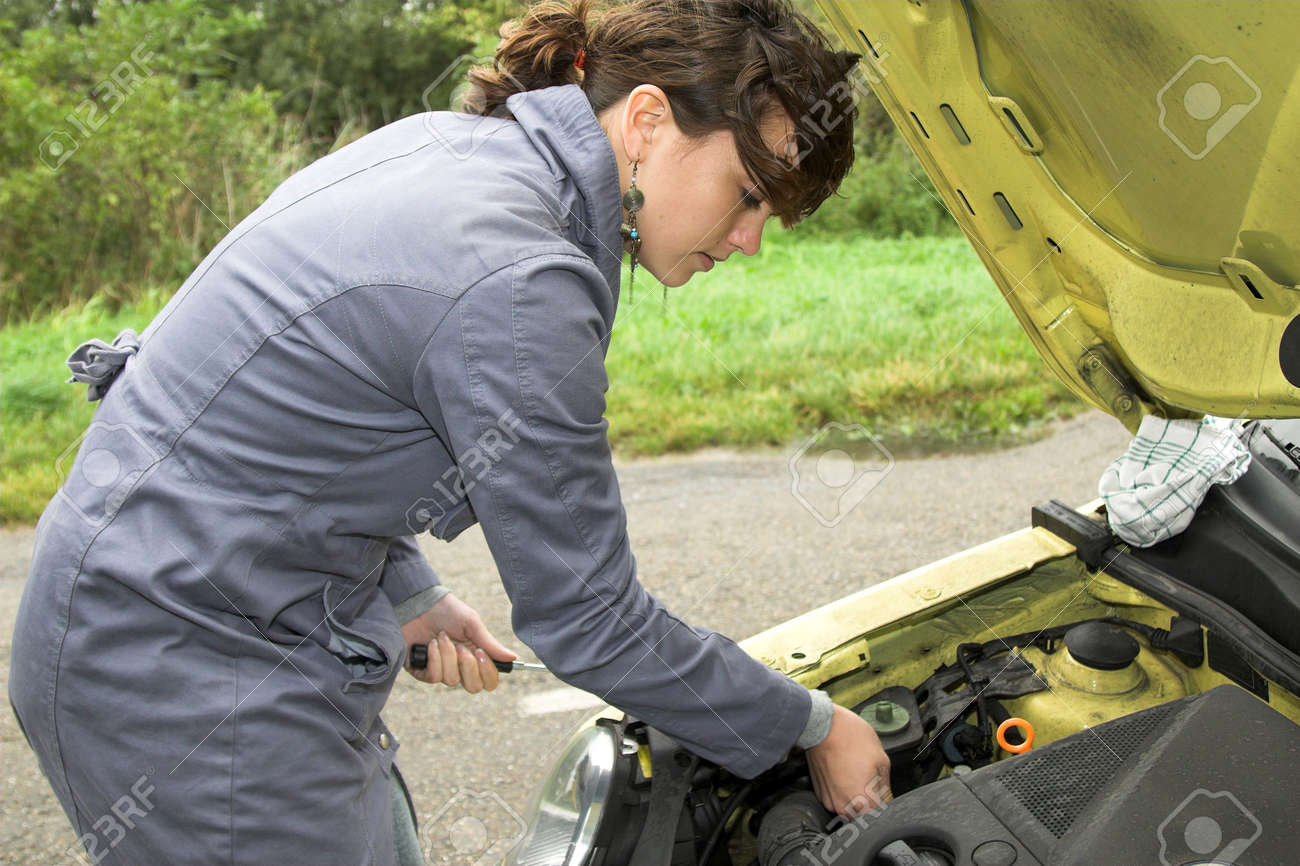 Pretty brunette trying to fix her car that has broken down along the road Stock Photo - 585188