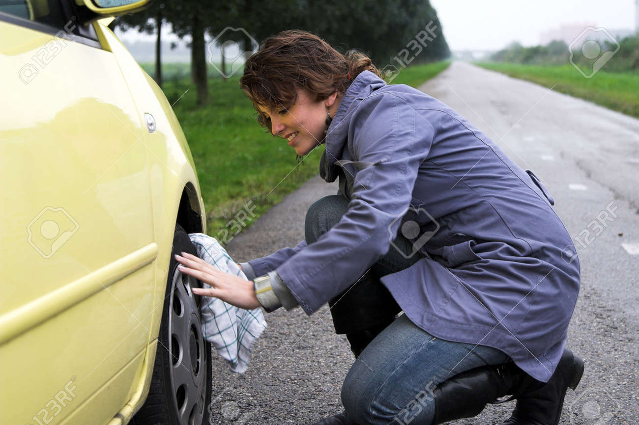 Pretty brunette checking her tires on a empty road Stock Photo - 585190