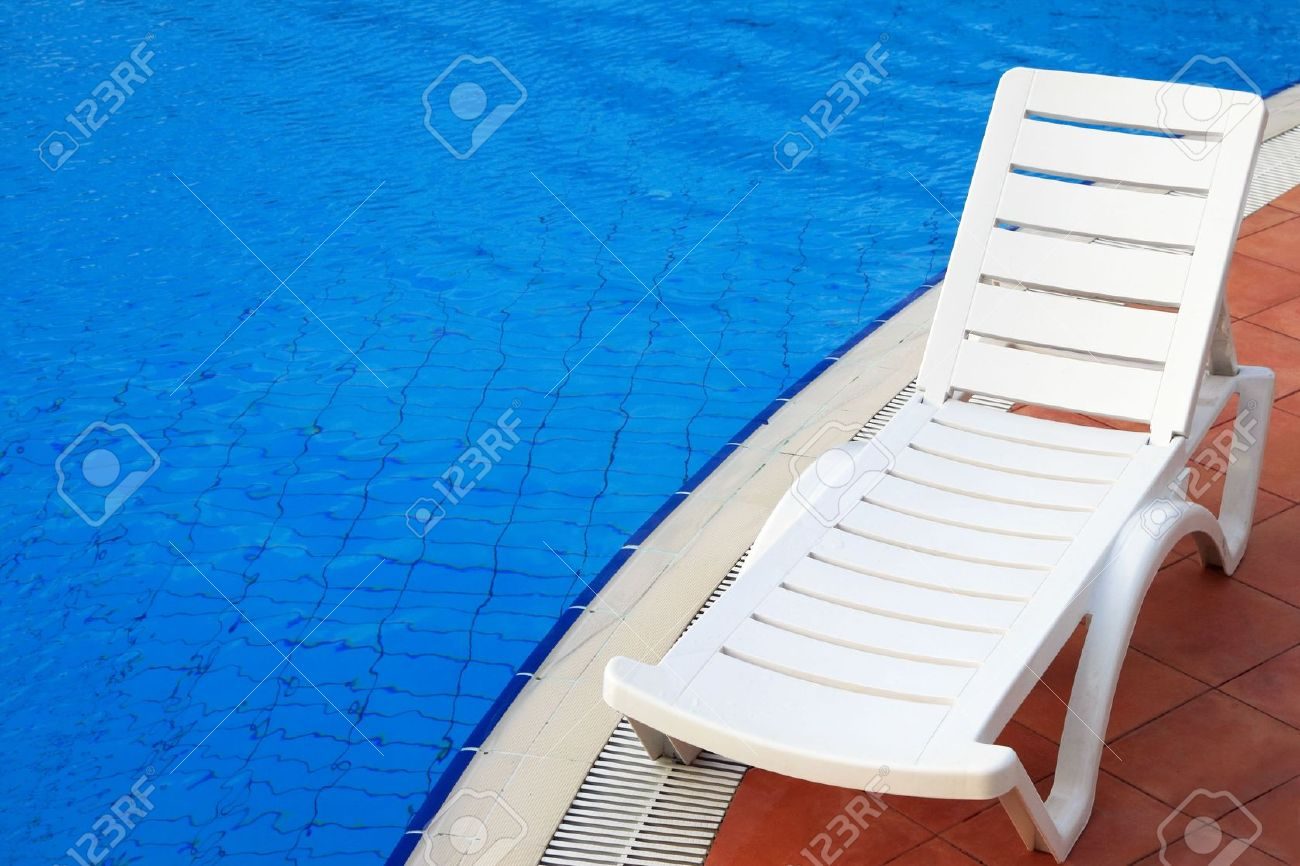 lounge chairs in a swimming pool invite you to relax stock photo