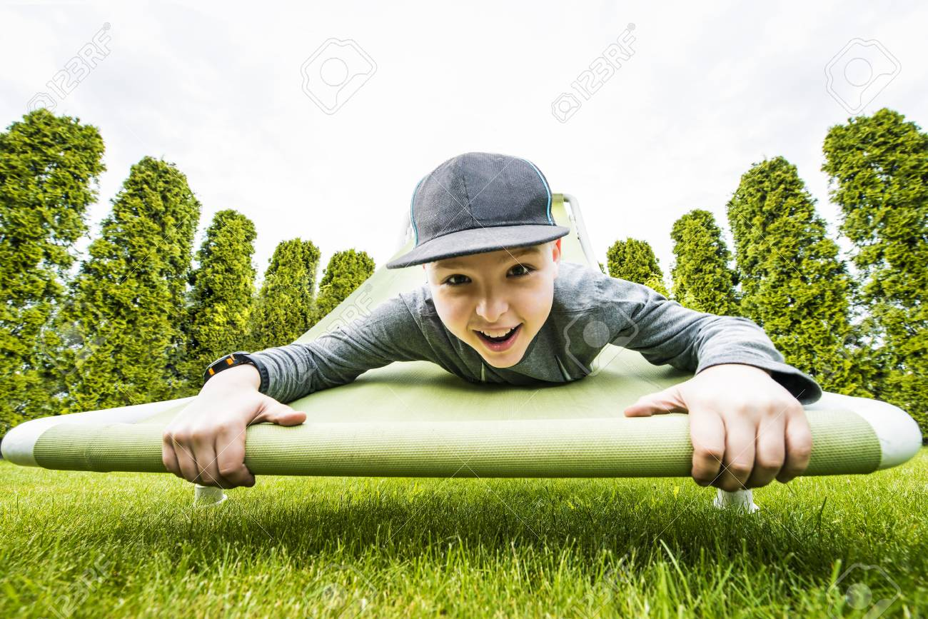 Young Boy Hanging Down On Raised Hammock Chair In The Green Garden