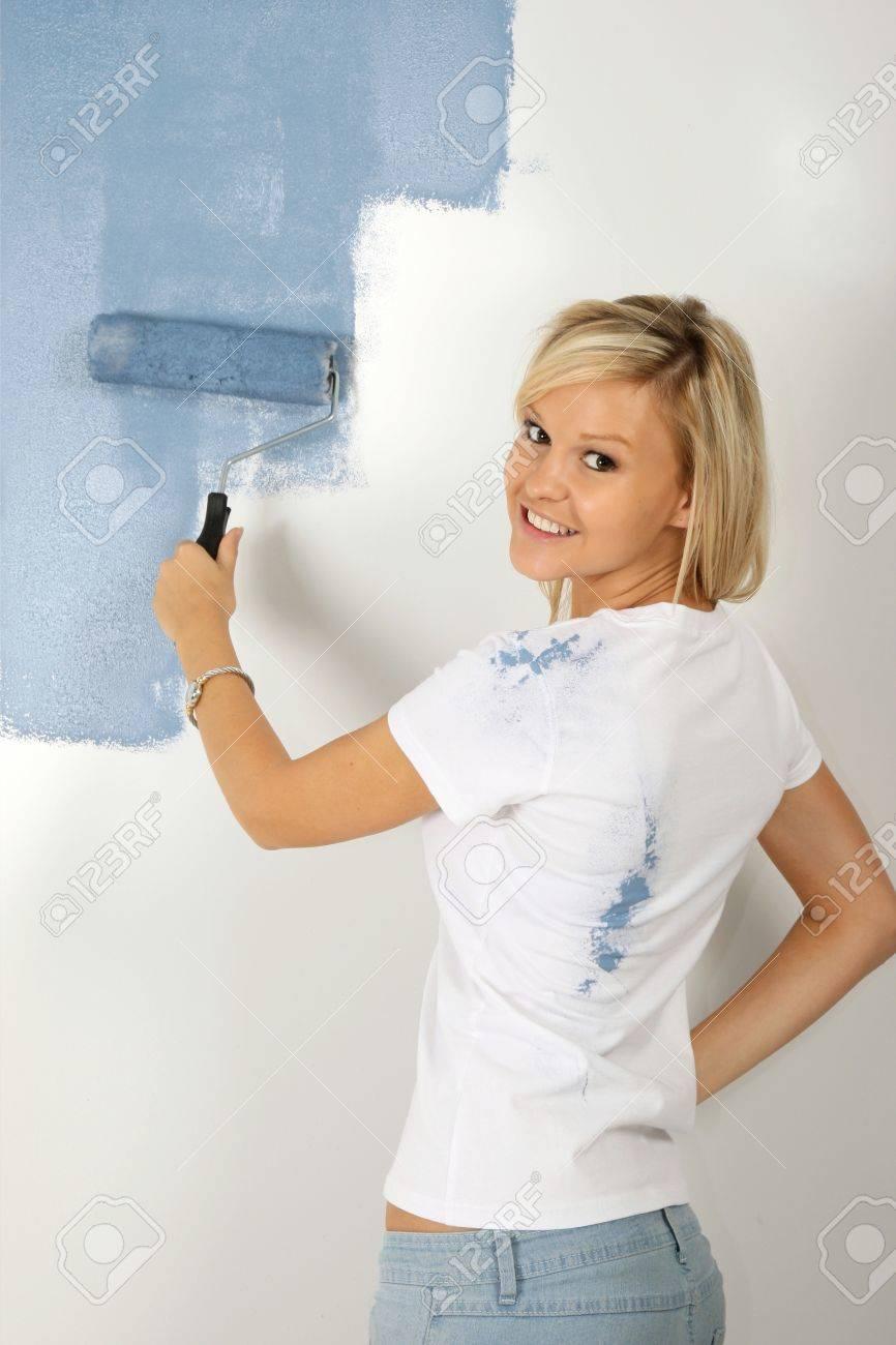 Mooie blonde dame schilderen een slaapkamer kamer poeder blauwe ...