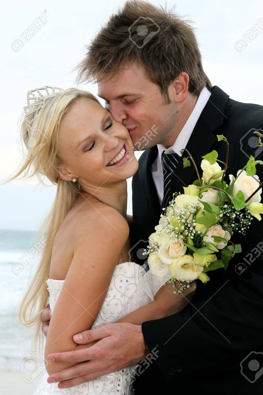 Pretty blond bride and her groom at the sea shore Stock Photo - 11744641