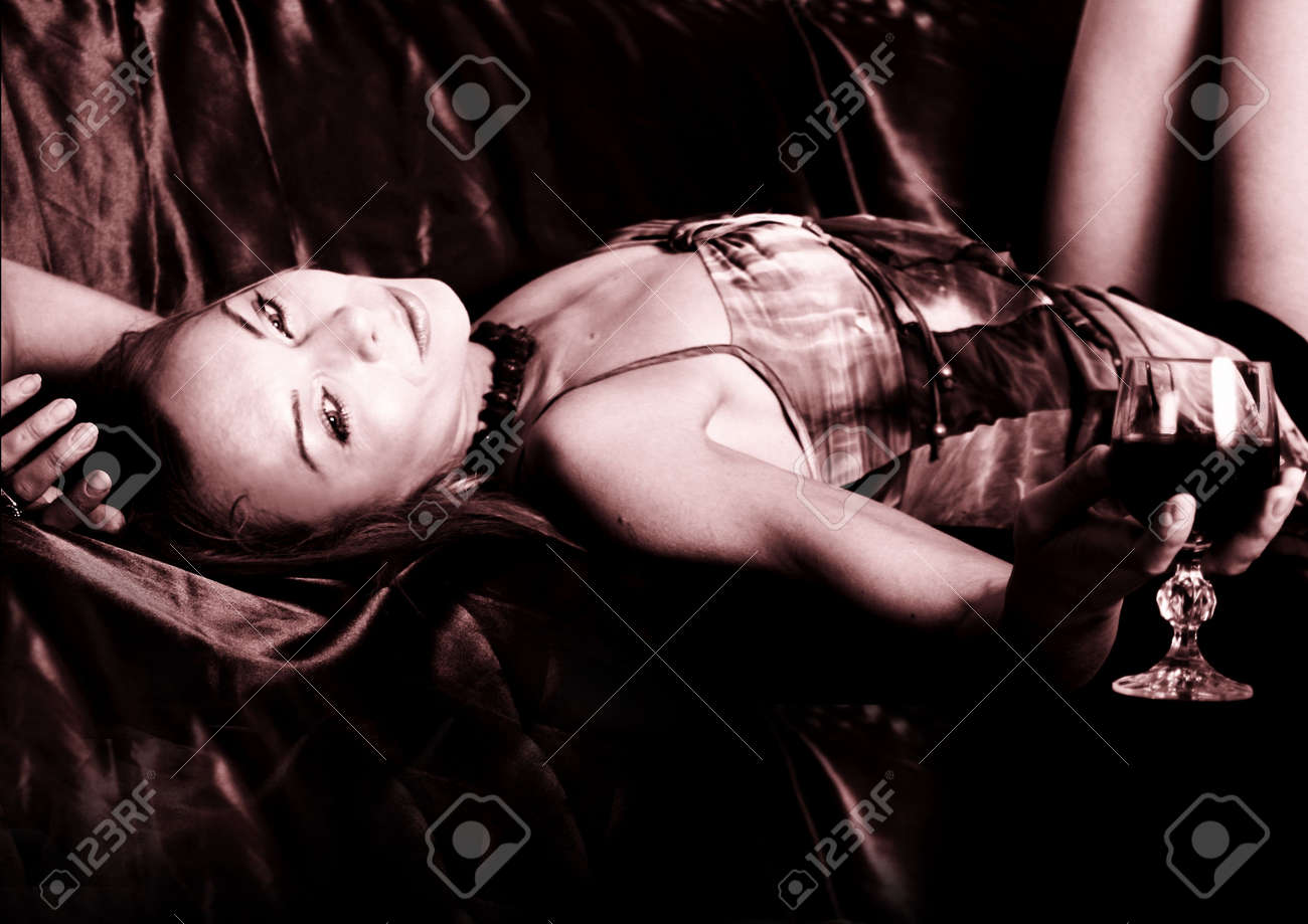 Young woman lying on sofa with a glass of wine Stock Photo - 1165499