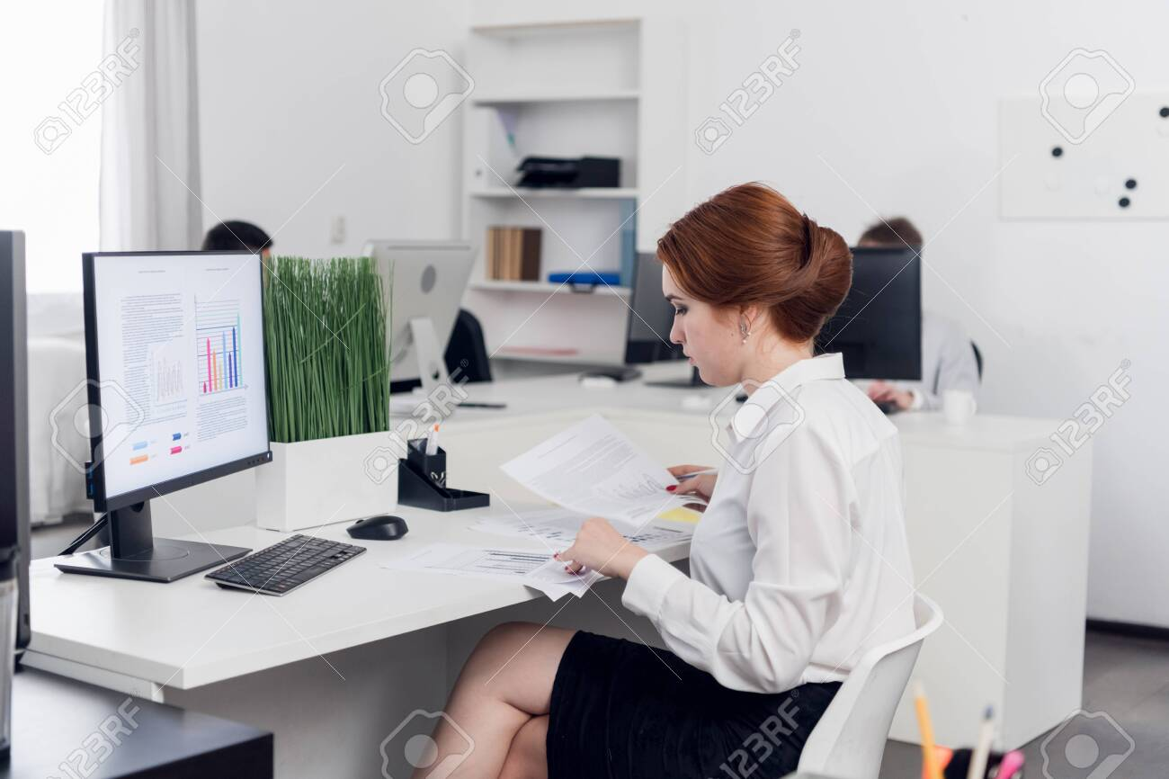 A Young Accountant In The Office Examines Accounting Financial Tax Reports  In The Office Of A Commercial Company. Mockup Monitor Stock Photo, Picture  And Royalty Free Image. Image 154869612.