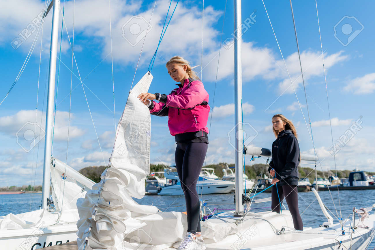 Two young female athletes prepare a sailing boat for the regatta on the river pier. - 159828708