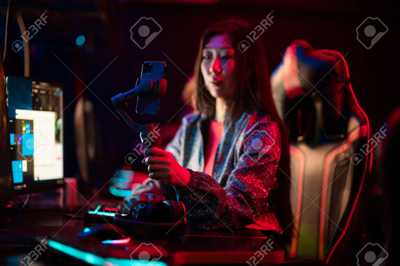 A young chinese gamer participates in esports competitions. Conducts an online broadcast and stream on a social network. Gimbal and smartphone. - 170401108