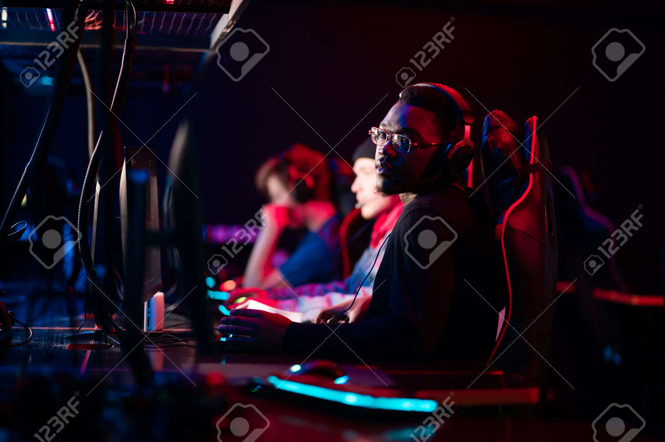 A member of the esports team at a bootcamp training session. Portrait of a black guy with glasses at a gaming computer with a glowing keyboard. - 170401109