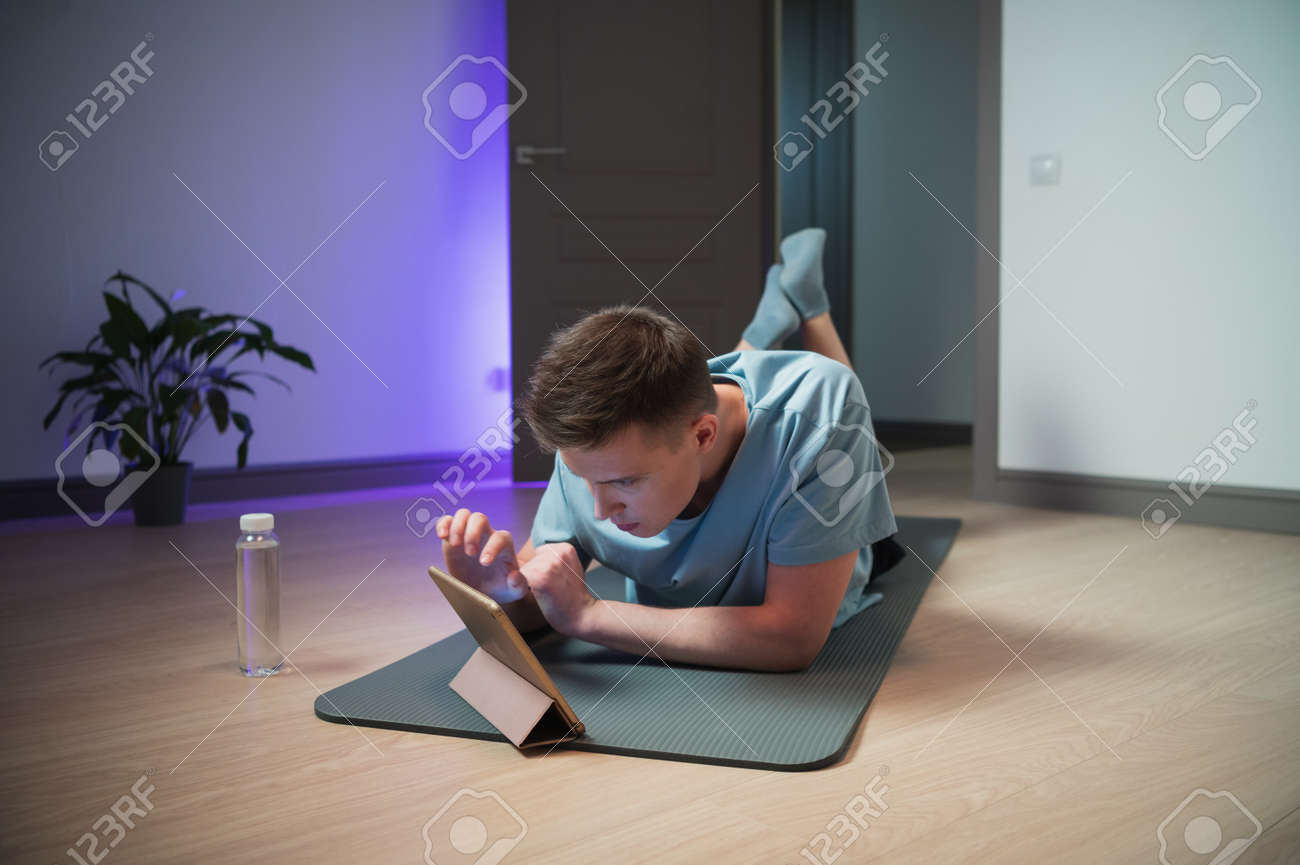 During a home workout, a pretty guy got a call from a girl on the tablet, he talks to her while lying on the mat - 170401080