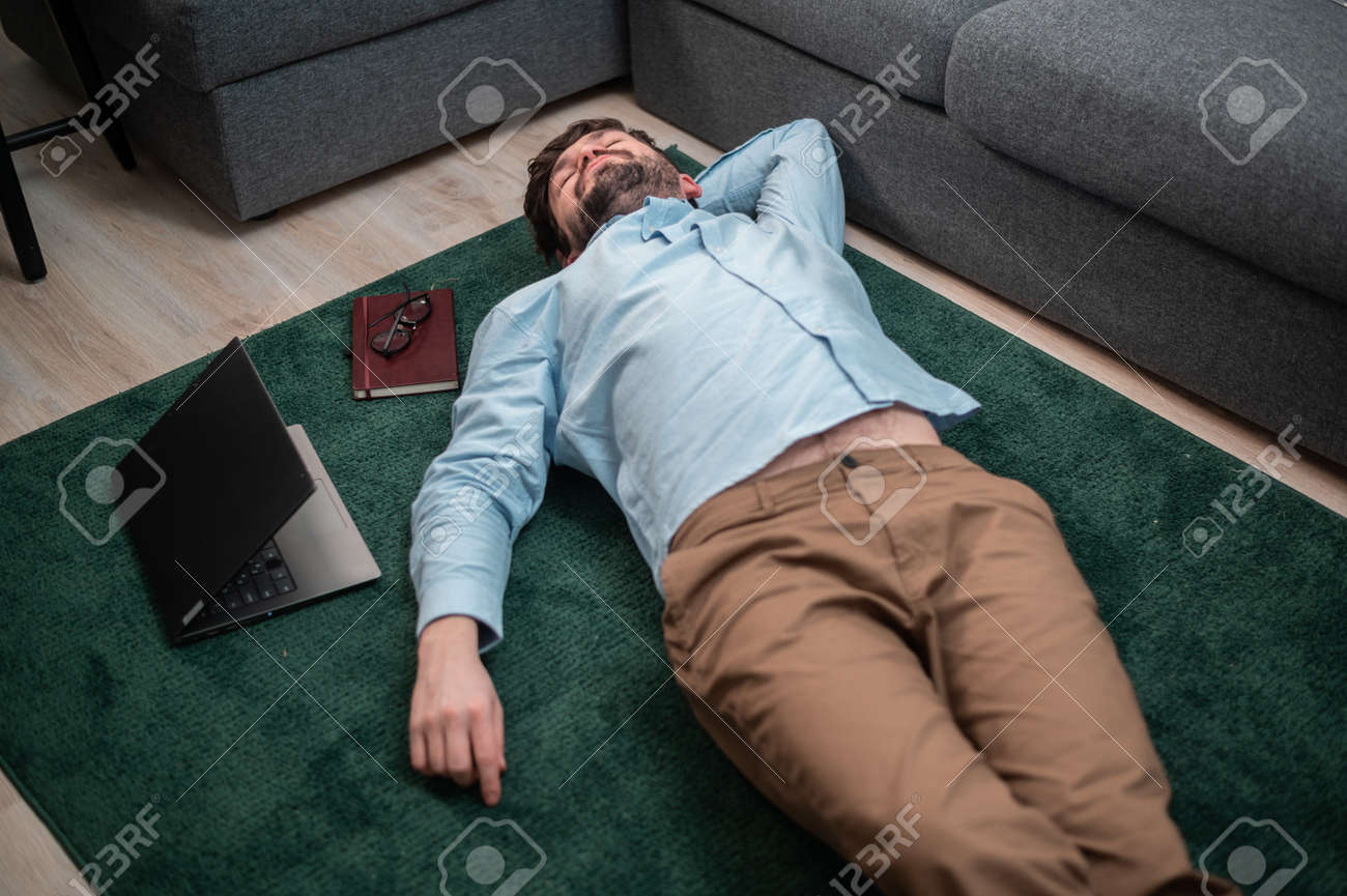 Young cute office worker lies on the floor mat next to the sofa, he is tired and asleep, top view - 170401090