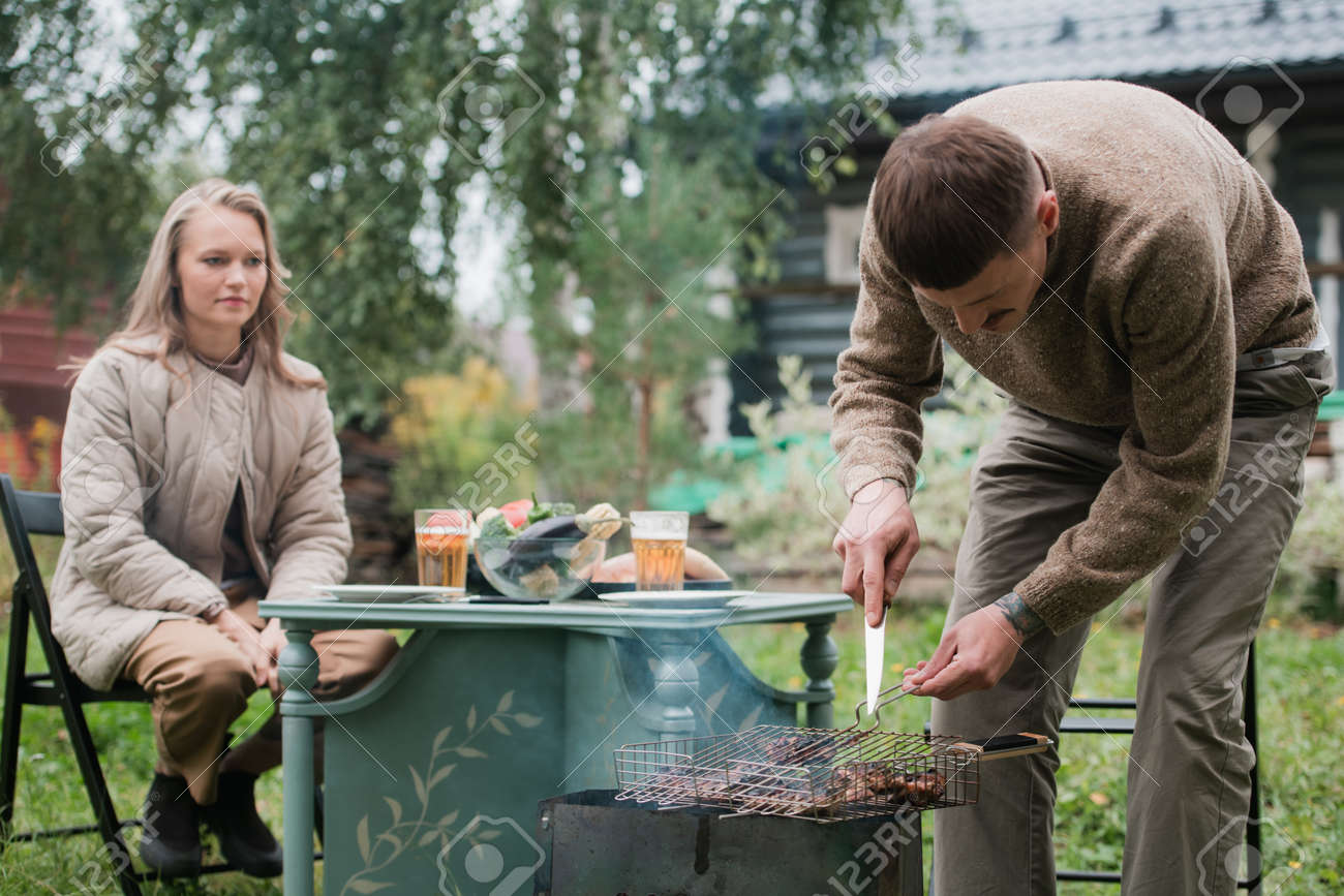 A young eastern european man prepares a barbecue, roasts fragrant meat on the grill. Concept of a romantic picnic for a young couple. - 170401053