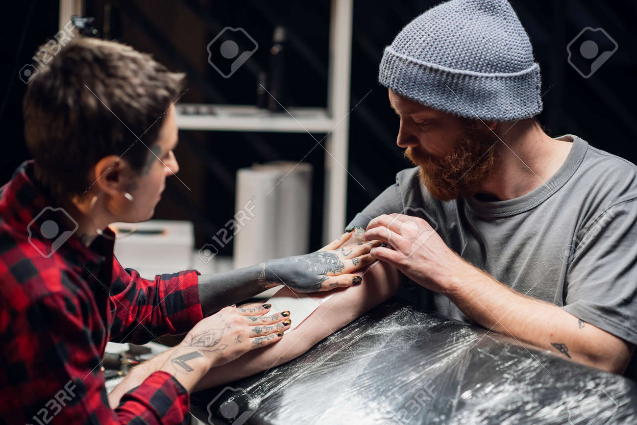 Girl tattoo artist takes care of the young mans hand after tattooing. Makes the dressing transparent film with the application of a moisturizer. - 170401059