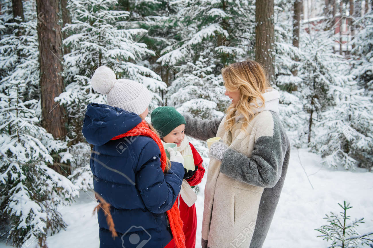 A young happy family with two children spends time outdoors in the winter forest. They drink hot tea from a thermos and mugs. - 170401063
