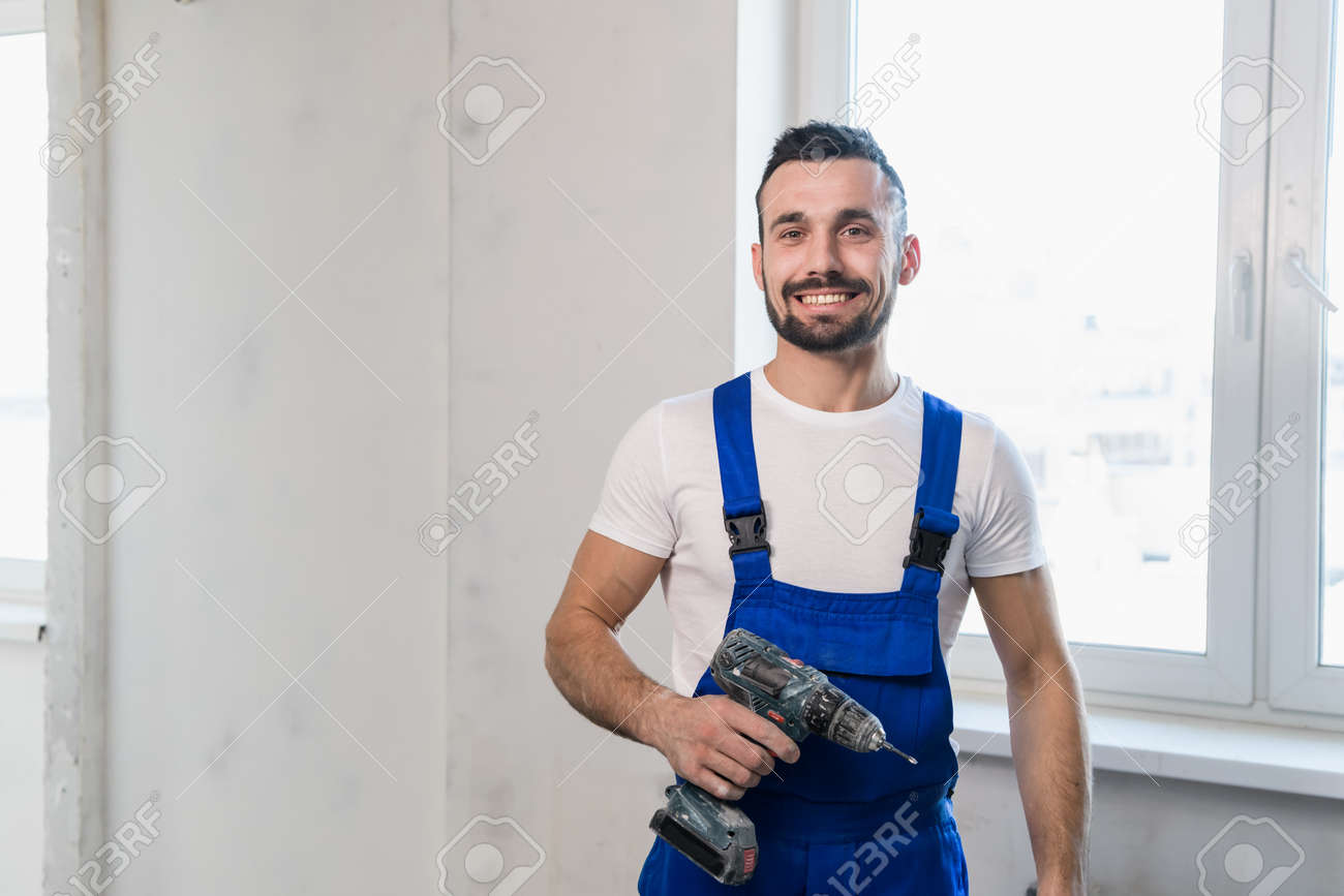 Handsome worker holds a drill in his hand - 170401066