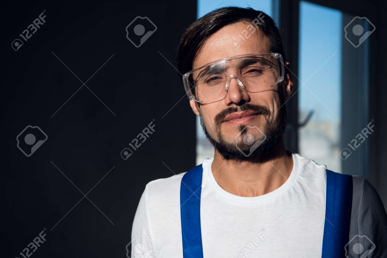 Repairer in blue overalls, white shirt and goggles - 170308238