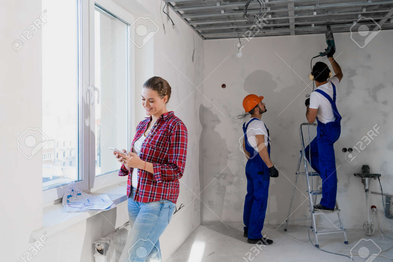 Builders use drill and stepladder, woman typing on the phone - 170308295